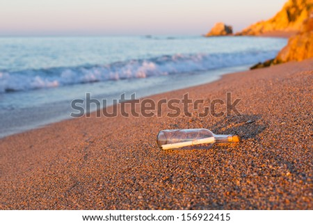 Bottle with message inside on the shore at the beach - stock photo
