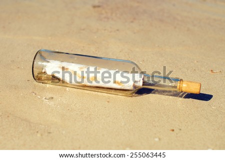Bottle with message on the beach. - stock photo