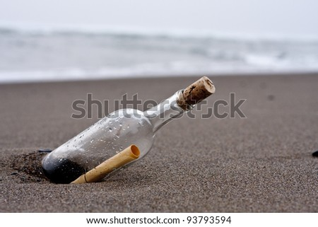 bottle with message on the beach - stock photo