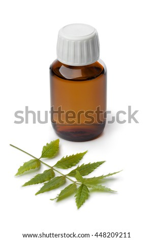 Bottle with Neem oil and green twig on white background - stock photo