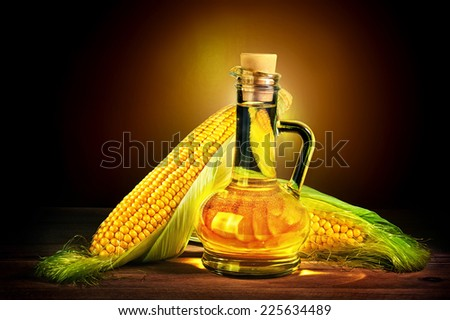 Bottle with oil and a corncob - stock photo