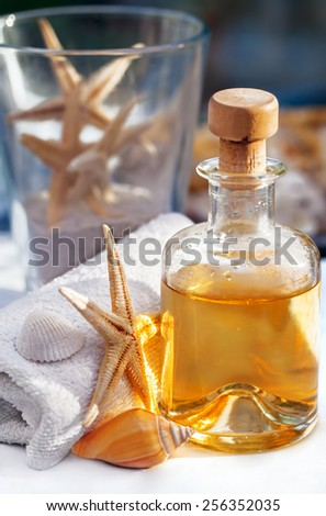 Bottle with oil for massage, aromatherapy and a towel, starfish and snail decoration - stock photo