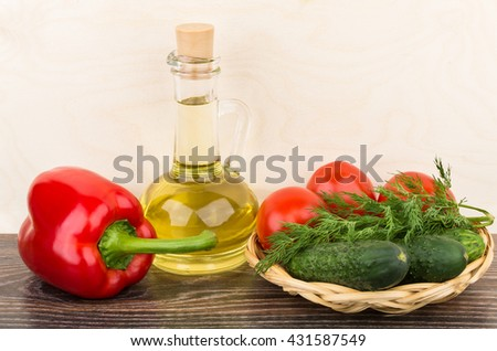 Bottle with oil, paprika and tomatoes, cucumbers, dill in wicker basket - stock photo