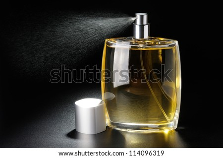 Bottle with perfume close up on black background - stock photo