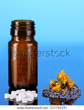 bottle with pills and herbs on blue background. concept of homeopathy - stock photo