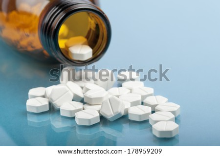 bottle with pills and tablets on blue background - stock photo