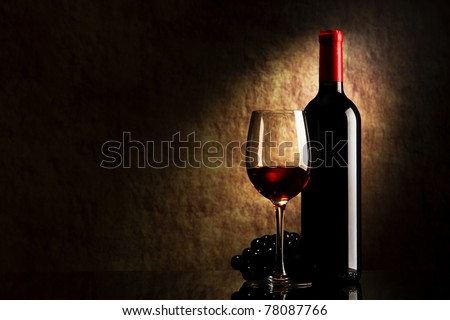 bottle with red wine and glass and grapes on a old stone