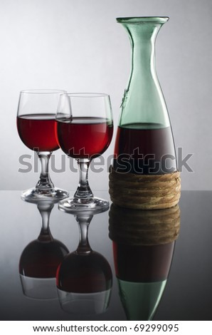 Bottle with red wine and glass close up