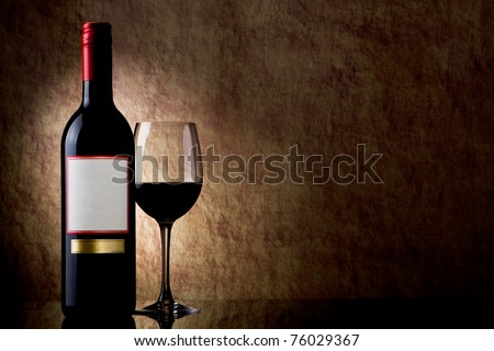 bottle with red wine and glass on a old stone - stock photo