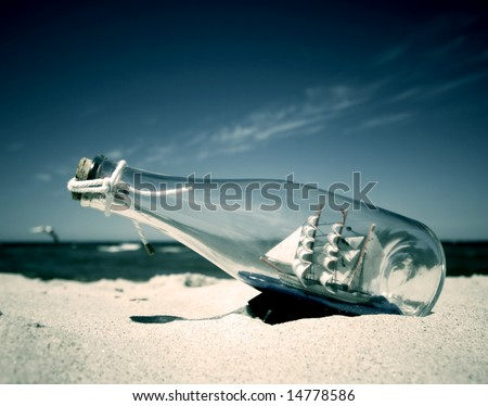 Bottle with ship inside lying on the beach. Conceptual image - stock photo