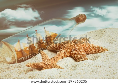 Bottle with ship inside on the beach with starfish - stock photo