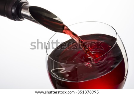 bottle with spout  pouring red wine into glass on white background - stock photo
