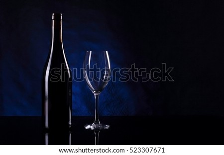 Bottle with vine and empty wineglass