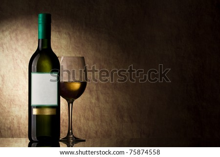 bottle with white wine and glass on a old stone - stock photo