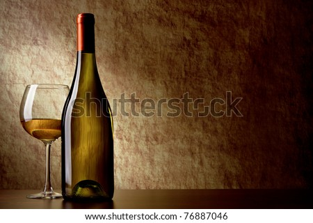 bottle with white wine and glass on a old stone. bottle in the foreground - stock photo