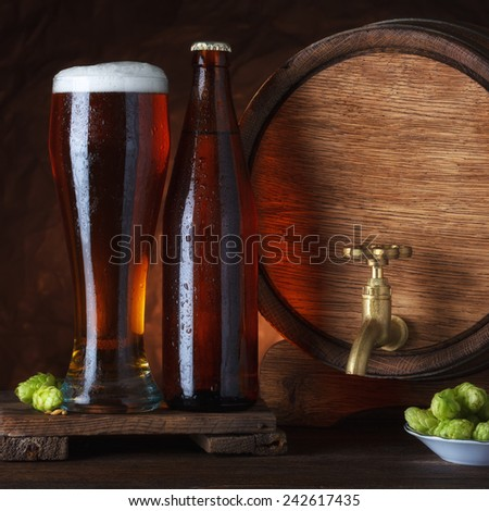 Bottled and unbottled beer glass with barrel and fresh hops for brewing on wooden table still-life - stock photo