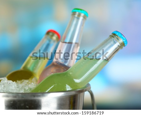 Bottled drinks in ice bucket on bright background - stock photo