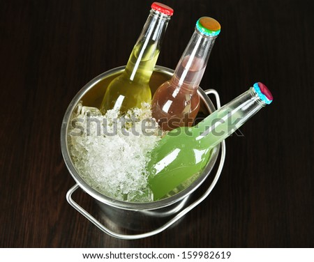 Bottled drinks in ice bucket on brown background
