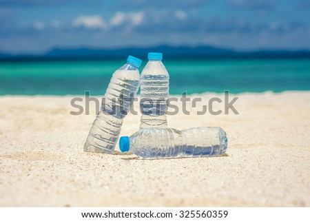 Bottled water on a hot day at the sand - stock photo