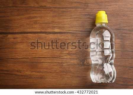 Bottled water on the wooden table, top view - stock photo