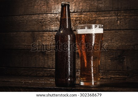 Bottles and glass of beer over wooden background - stock photo