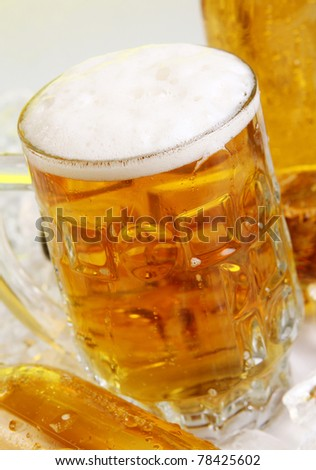 Bottles and Glass of beer with foam - stock photo