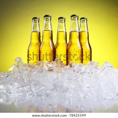 Bottles and Glass of beer with foam over yellow background - stock photo