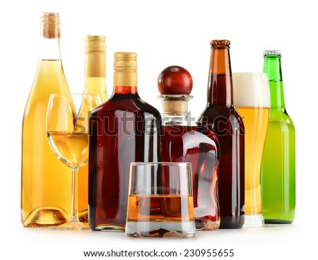 Bottles and glasses of assorted alcoholic beverages isolated on white background - stock photo