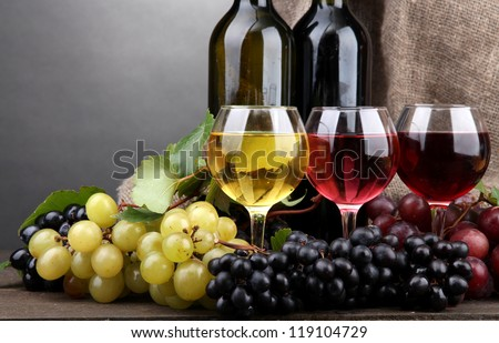 bottles and glasses of wine and grapes on grey background - stock photo