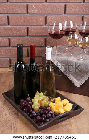 Bottles and glasses of wine, cheese and ripe grapes on table on brick wall background - stock photo
