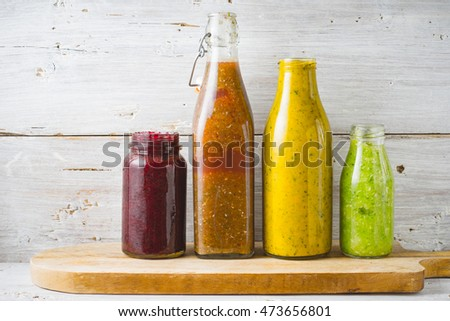 Bottles and jar with different smoothie on the white wooden background horizontal