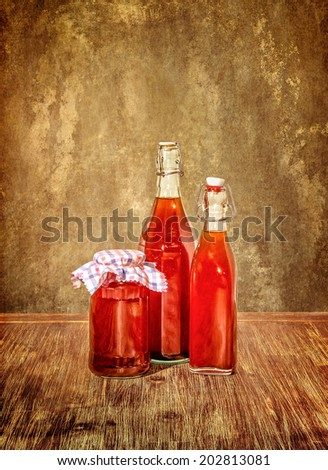 Bottles filled with yellow syrup and jam on kitchen table in vintage filtered style - stock photo