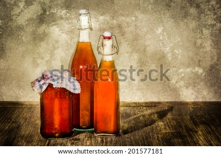 Bottles filled with yellow syrup and jam on kitchen table in vintage style - stock photo