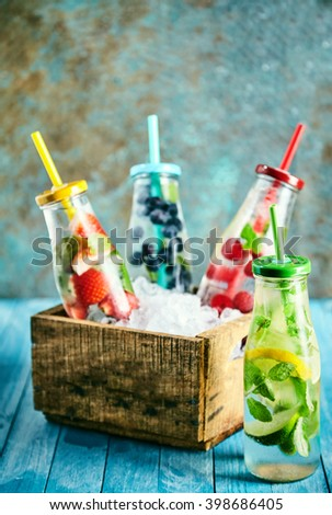 Bottles full of ice water and lime, lemon, strawberries, blueberries and raspberries in little box on top of wooden table - stock photo
