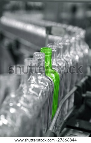 Bottles in a factory line, one different unique green
