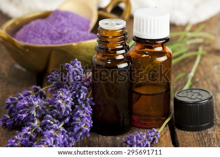 Bottles of aromatherapy essence and bath salt with lavender flowers closeup - stock photo