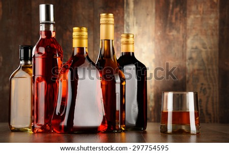 Bottles of assorted alcoholic beverages and glass of whisky - stock photo
