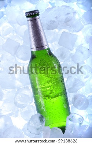 Bottles of beer in ice on blue background