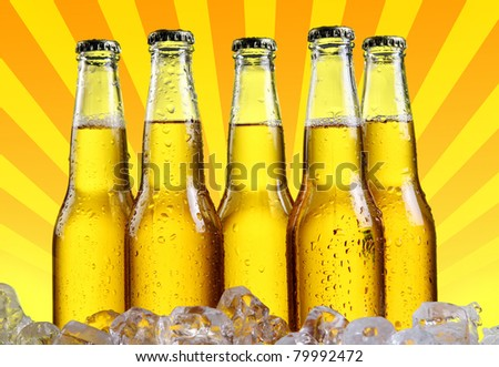 Bottles of beer in ice with abstract orange background - stock photo