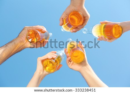 Bottles of beer in people's hands on blue sky background - stock photo