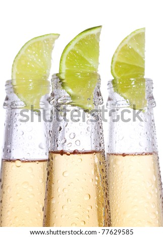 bottles of beer with lime on white background - stock photo