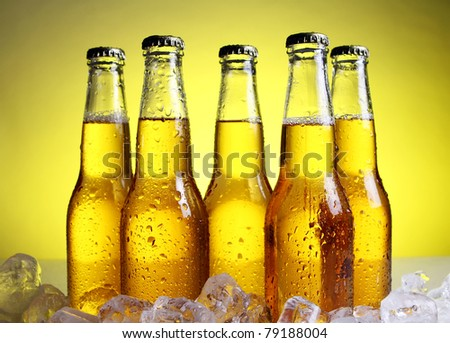 Bottles of cold and fresh beer with ice over yellow background - stock photo