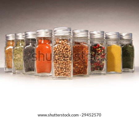 Bottles of colorful spices with grey background - stock photo