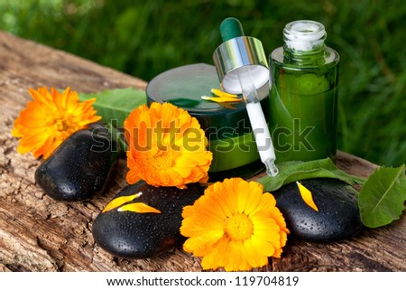 bottles of cream, serum with orange marigold flowers. spa concept - stock photo