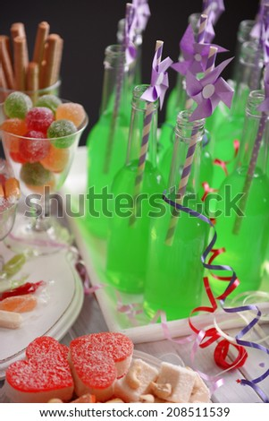 Bottles of drink with straw and sweets on dark background