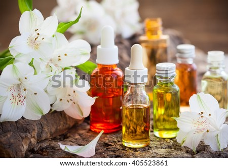 Bottles of essential aromatic oils and fresh flowers - stock photo