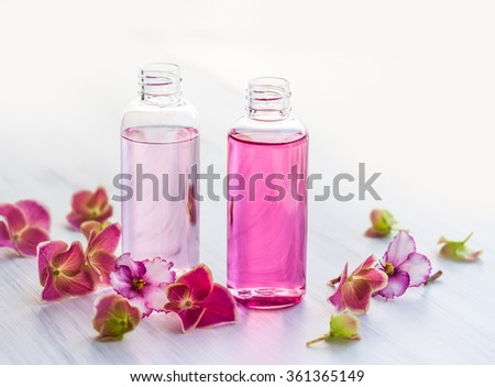 Bottles of essential aromatic oils surrounded by fresh flower - stock photo