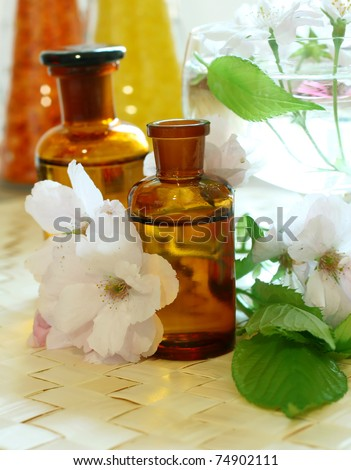 Bottles of essential oil and flowers - stock photo