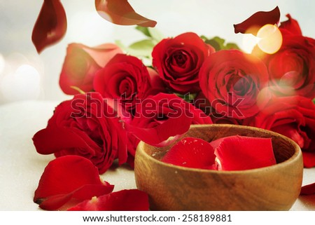 Bottles of essential oil and red rose - stock photo