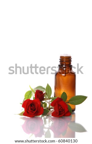 Bottles of essential oil and red rose with beautiful reflection - stock photo